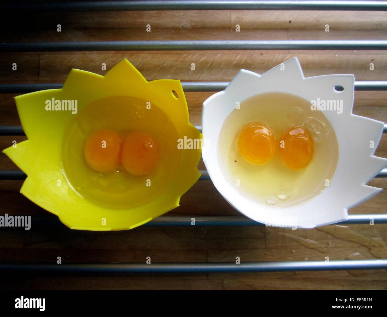 two double yoke eggs in poaching cups - Stock Image