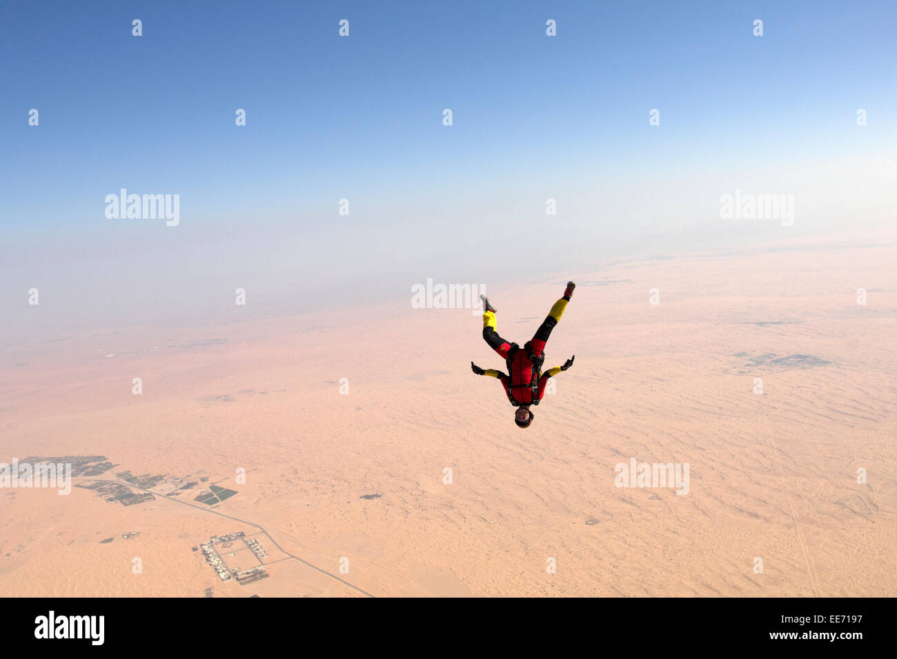 Skydiver in a freefly frog headdown position is flying over a big desert area. Thereby the girl is flying with over - Stock Image