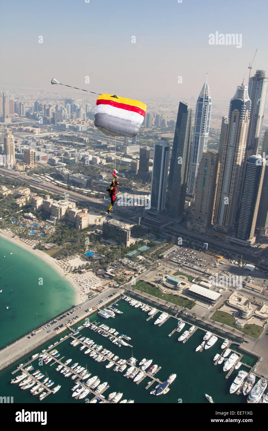 Skydiver under canopy is flying next to the Dubai sky scrapers. Thereby the parachutist has an amassing view over - Stock Image