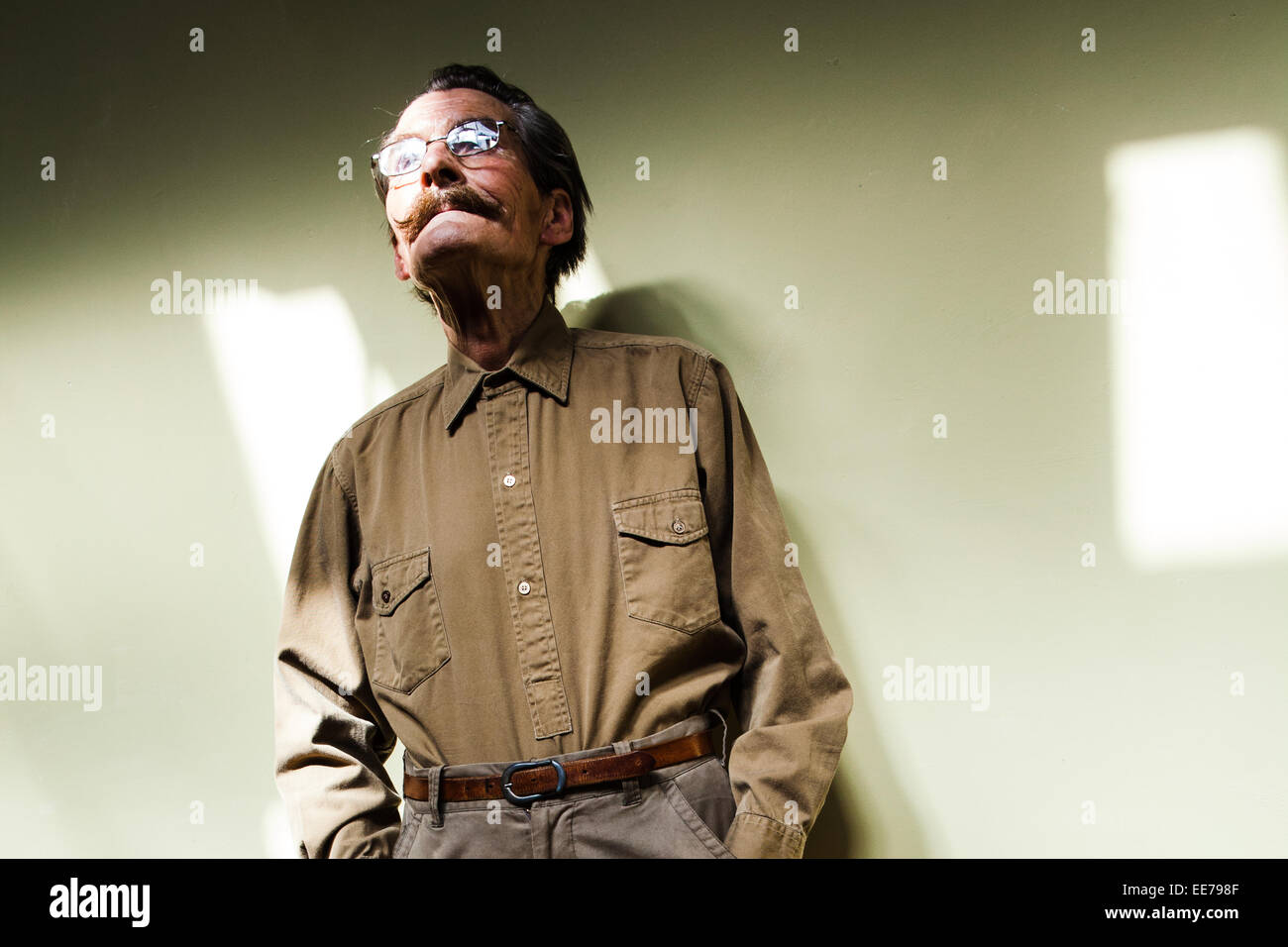 Man in his 60s with moustache wearing khaki shirt and trousers. - Stock Image