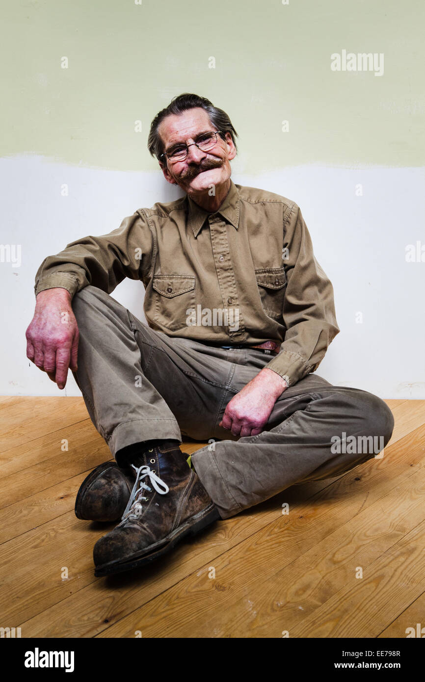 Man in his 60s with moustache wearing khaki shirt and trousers sitting on the floor. - Stock Image