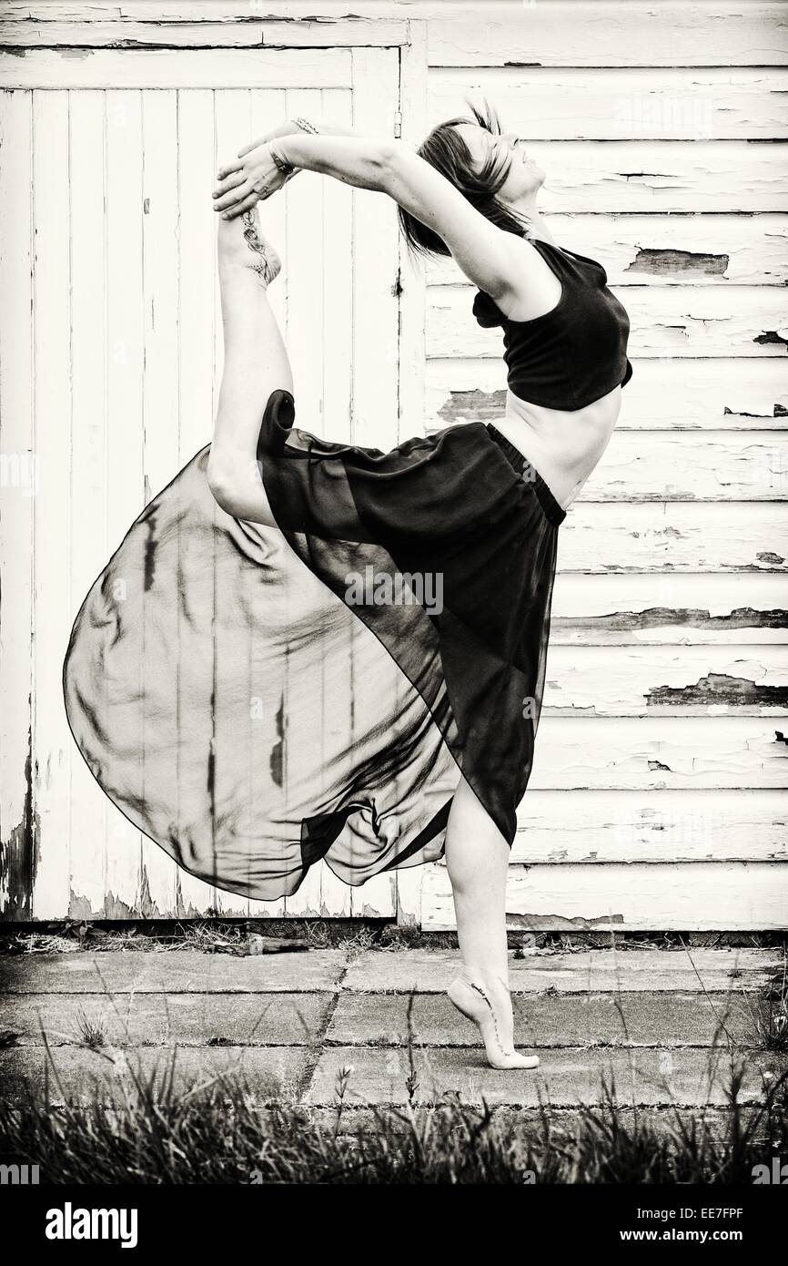 Female dancer warms up outside on concrete slabs, in front of a shed. - Stock Image
