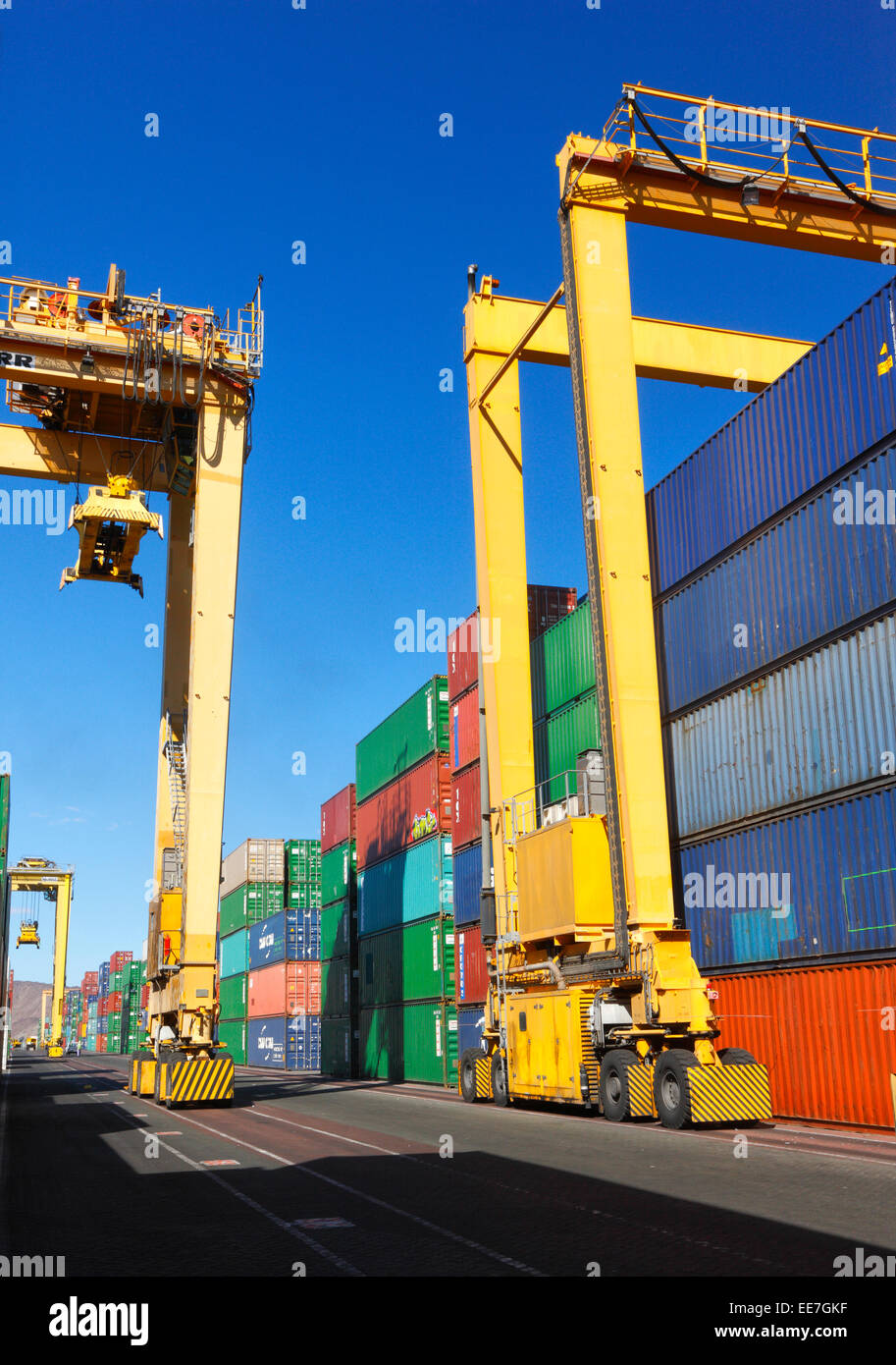 Commercial dock Khor Fakkan, with yellow crane and colorful containers - Stock Image