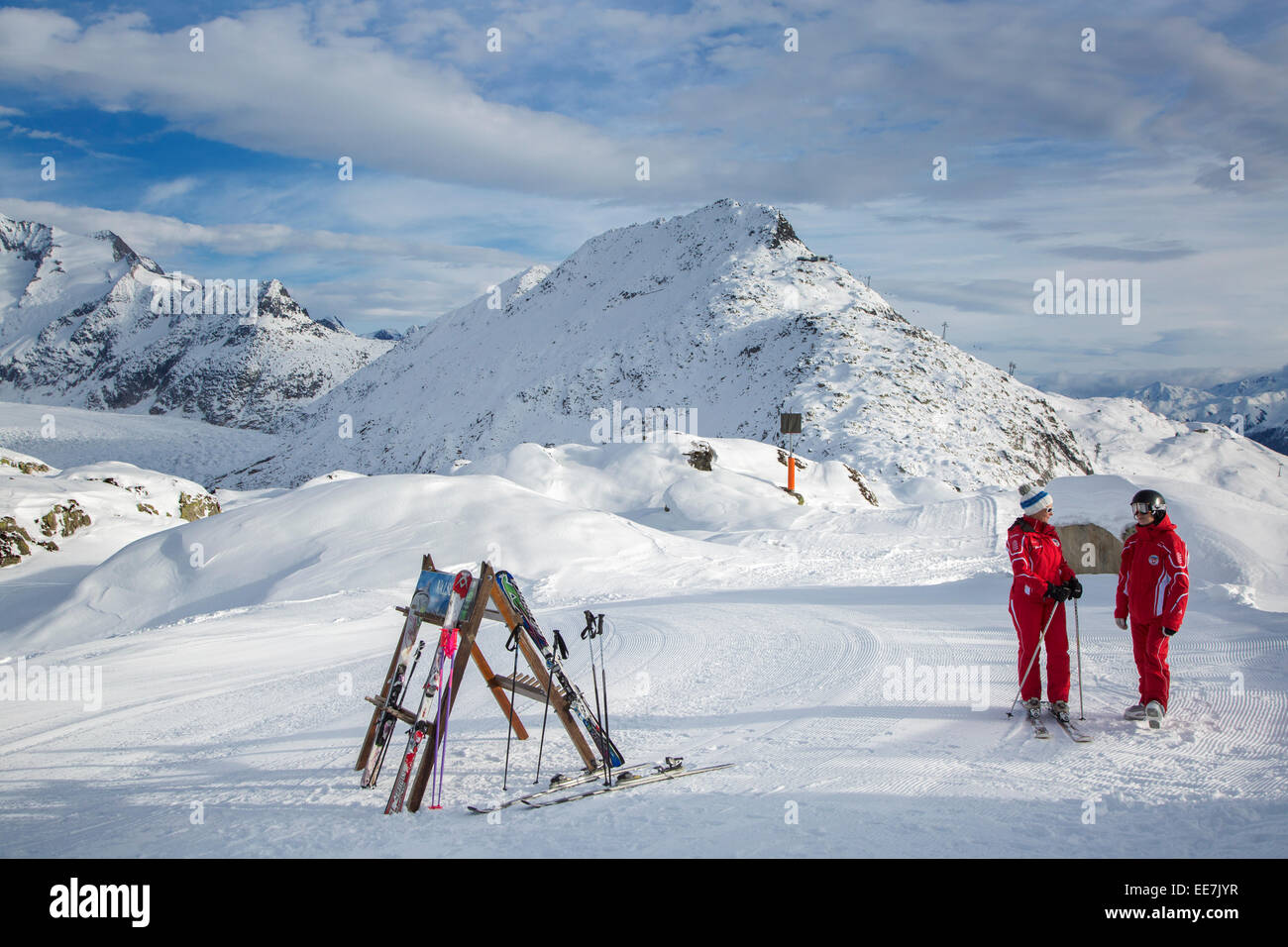 Two Swiss female ski instructors waiting on top of ski run in winter sports resort in the Alps, Wallis / Valais, - Stock Image