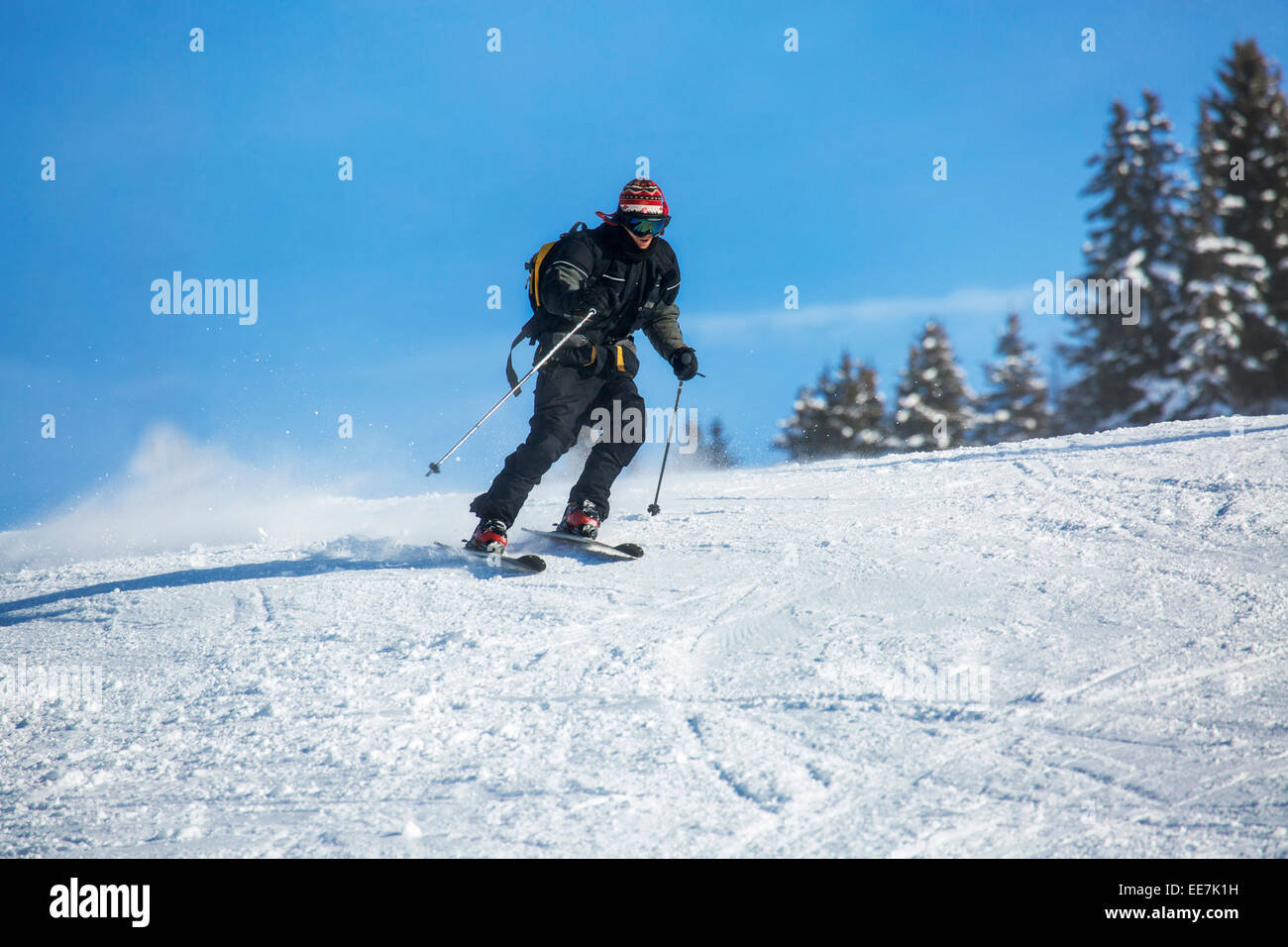 Skier with backpack skiing down ski slope in winter sports resort in the Alps - Stock Image