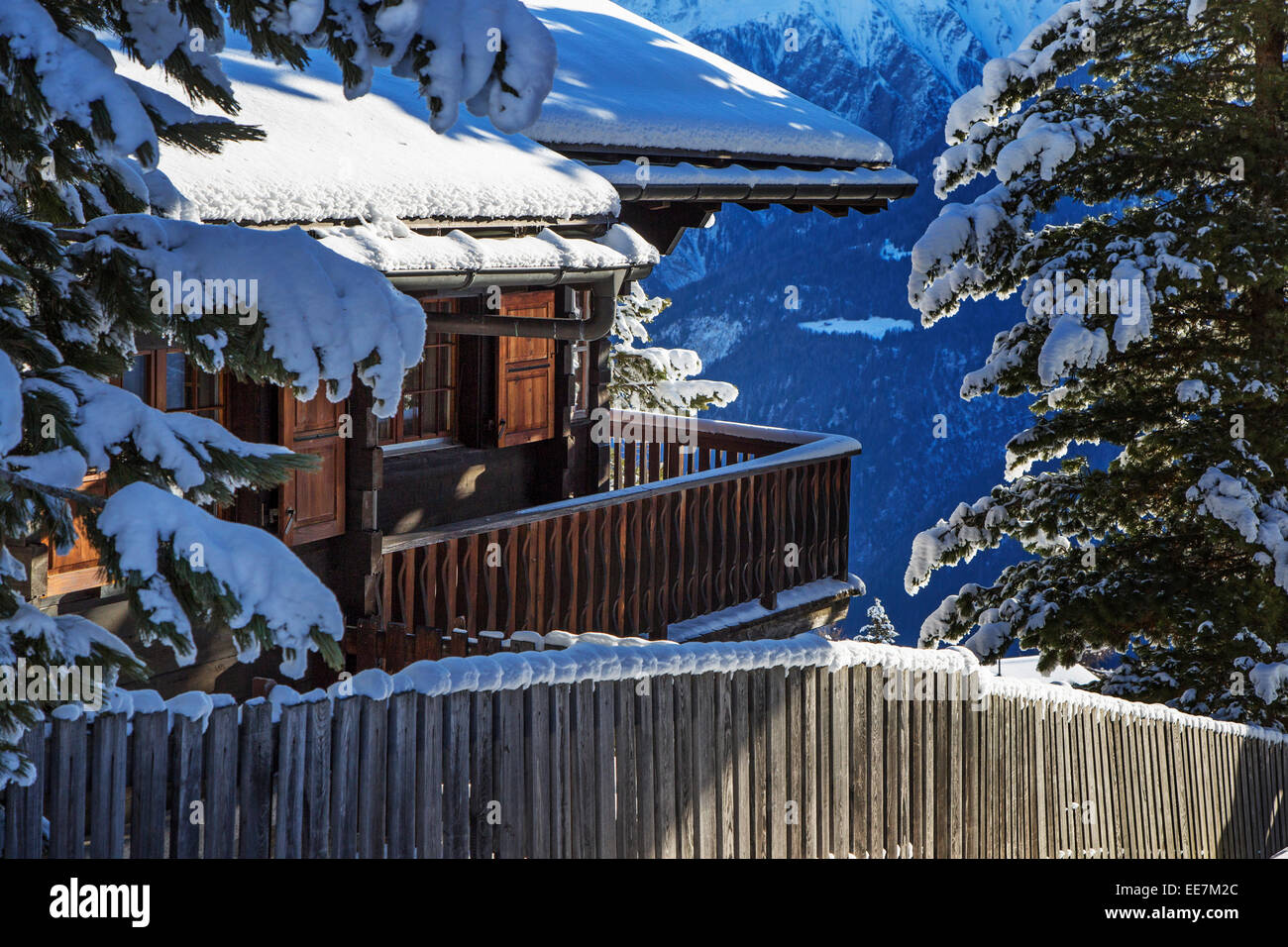 Snow covered Swiss wooden chalet in winter in the Alps, Wallis / Valais, Switzerland - Stock Image