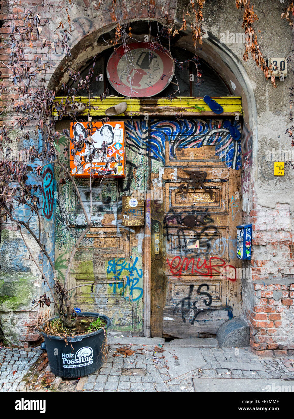 Building entrance door covered in graffiti, stickers, old shoes and dead plants, Tucholskystrasse, Mitte, Berlin - Stock Image