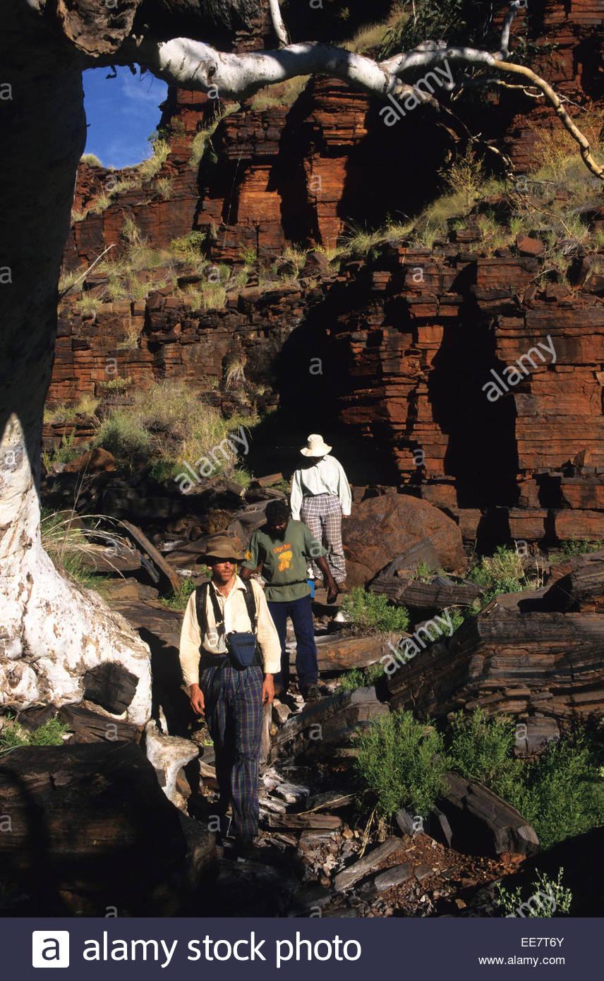 Trekkers climbing  in Karijini National Park, Australia. - Stock Image