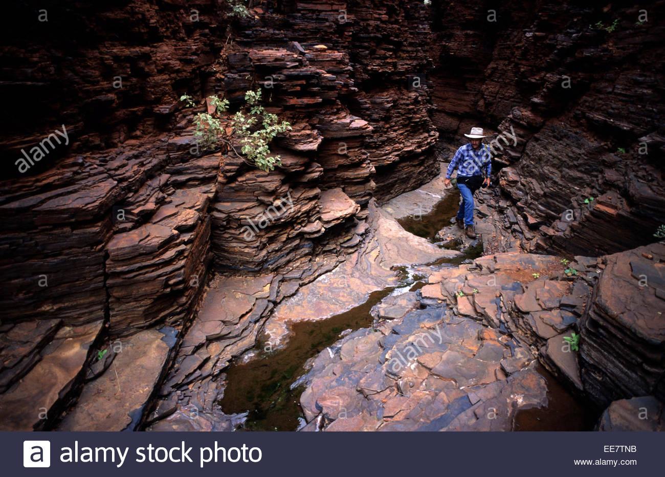Trekker climbing in Karijini National Park, Australia. - Stock Image
