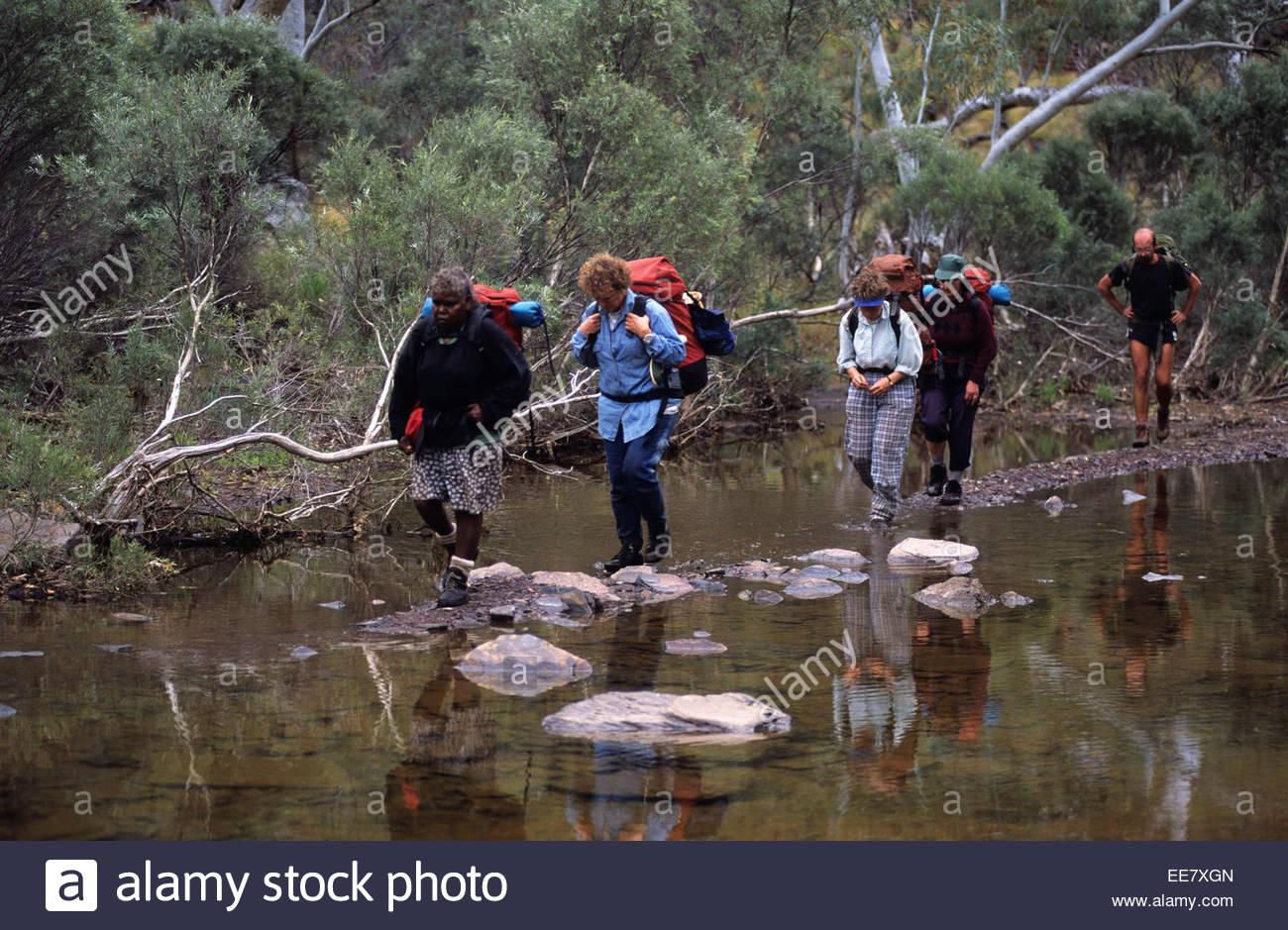 Trekkers walking along a river  in Karijini National Park, Australia. - Stock Image