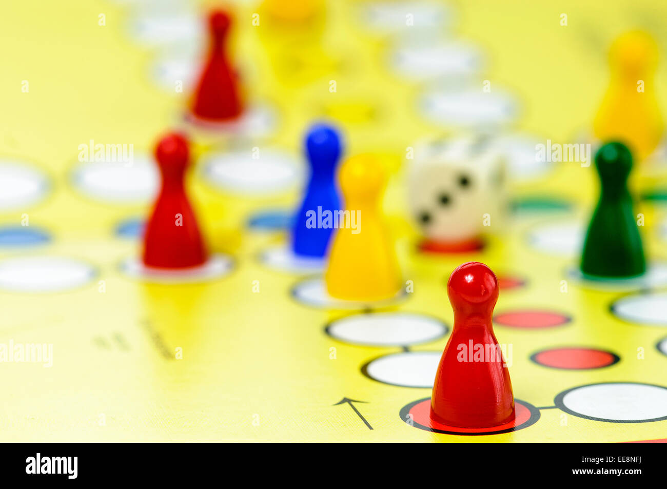 Pieces and a die on a Ludo board game Stock Photo