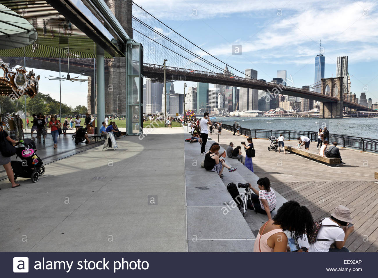 Empire Fulton Ferry park in DUMBO with Jane's carousel and view on downtown Manhattan and the Brooklyn Bridge - Stock Image