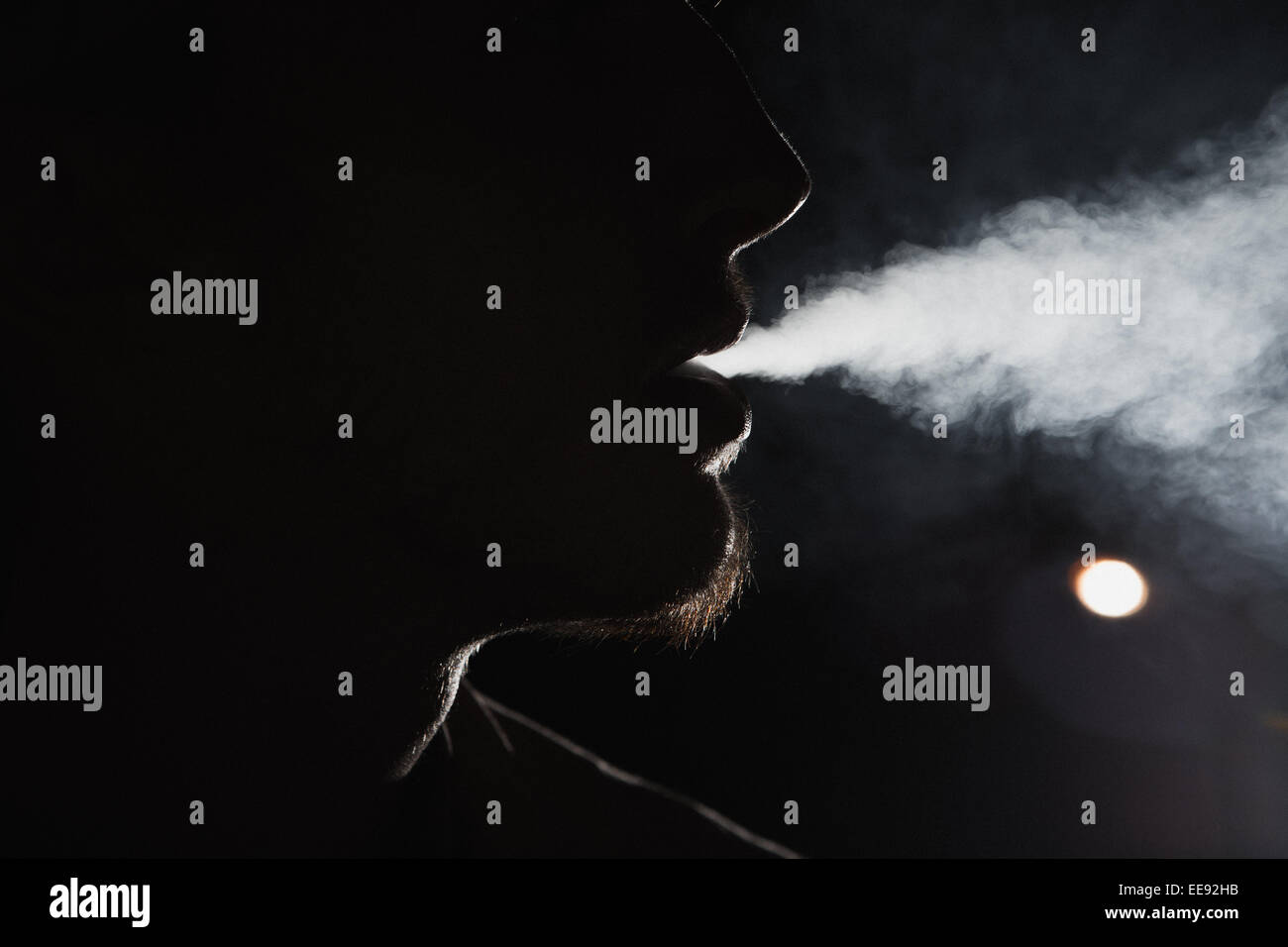 Close up portrait of young man smoking cigarette Stock Photo