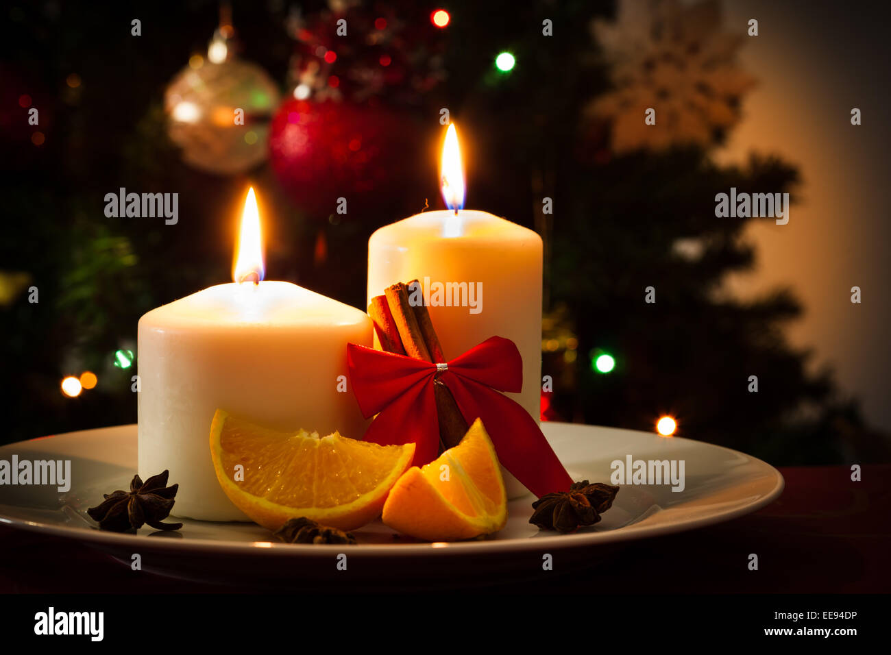 Christmas decoration, candles, cinnamon sticks and pieces of orange ...
