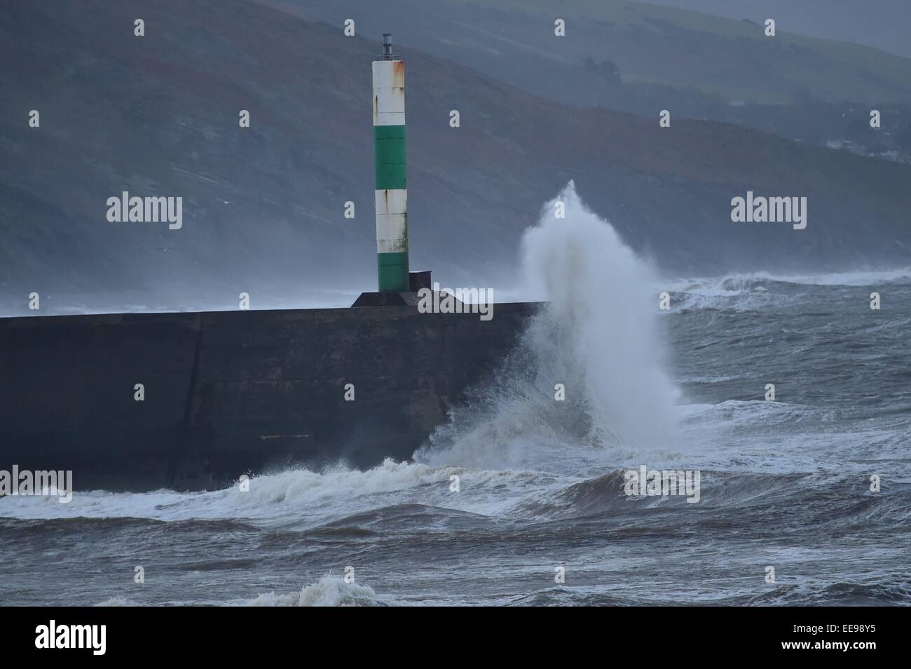 Aberystwyth, Wales, UK. 15th January, 2015. UK weather. Waves crash over the harbour wall and lighthouse beacon - Stock Image