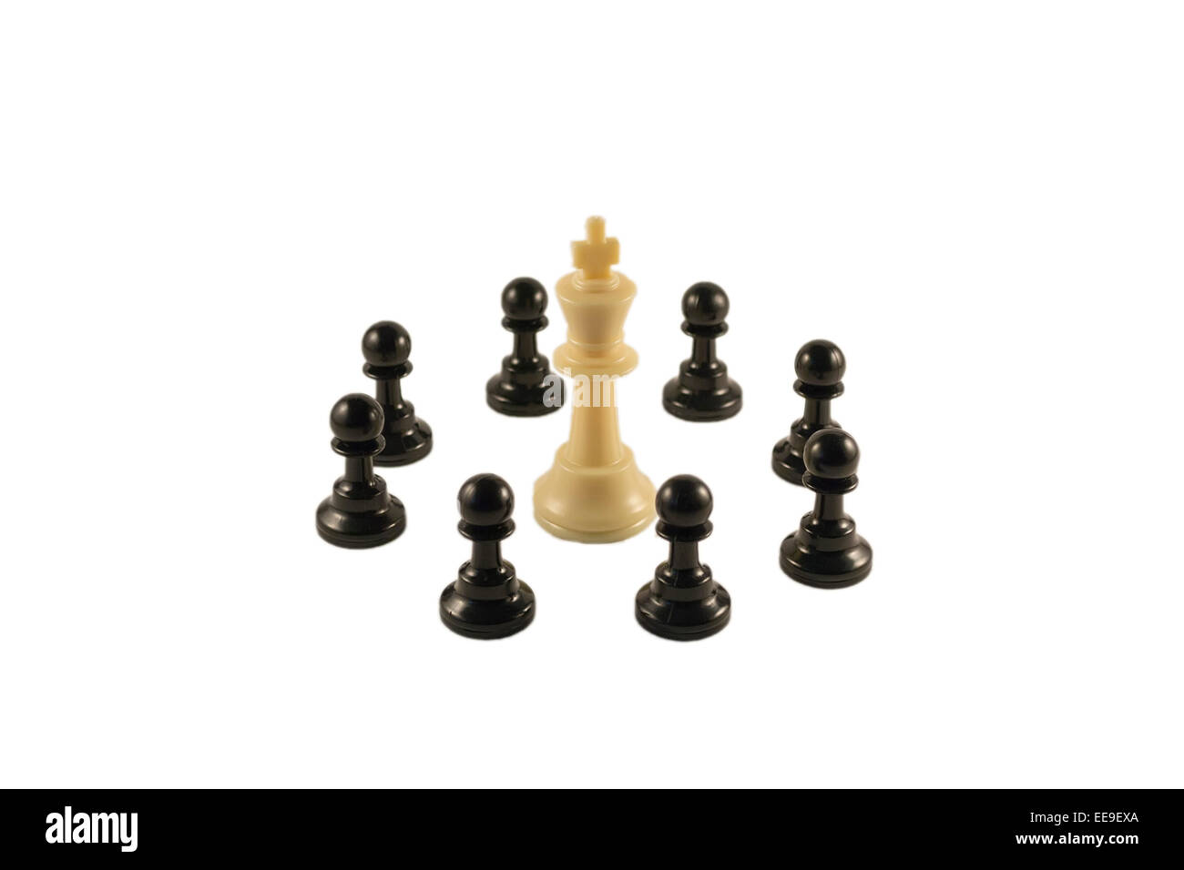 White king surrounded by the black pawns in a circle formation - Stock Image