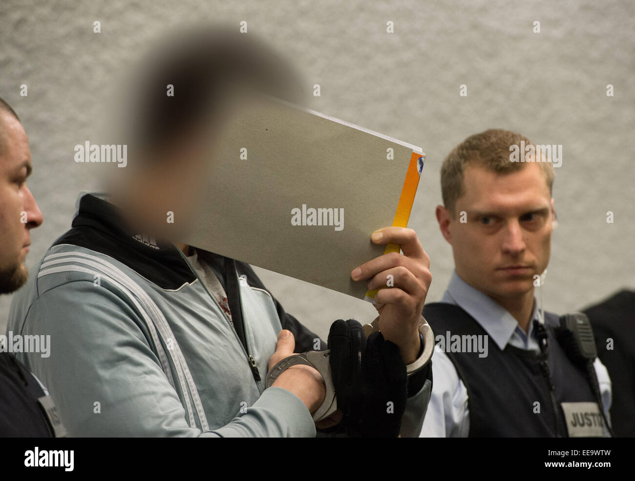 A defendant stands between justice officials before the start of the trial against four neo-Nazis at the district Stock Photo