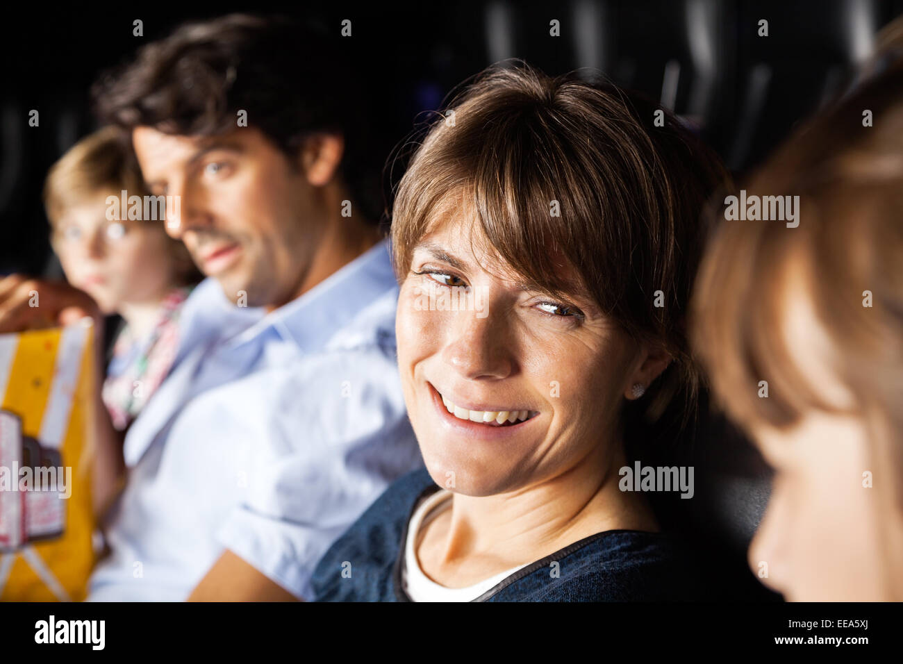 Happy Woman Talking To Daughter While Watching Movie In Theater - Stock Image