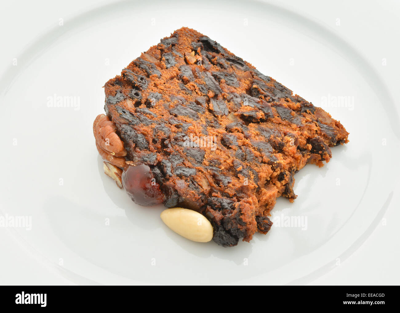 Slice of homemade fruitcake decorated with nuts and cherries on white plate - Stock Image