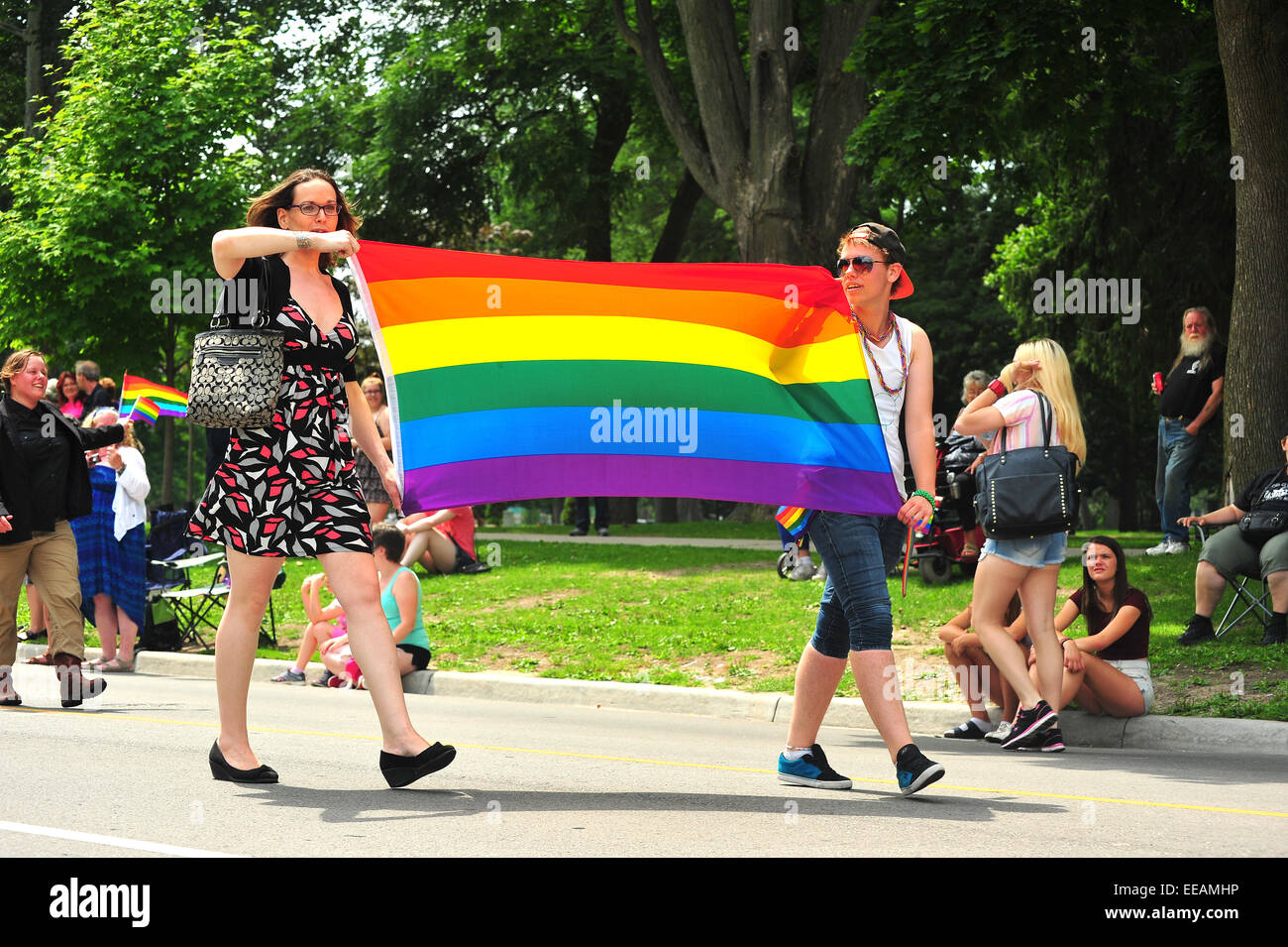 Women carrying the rainbow pride flag during a pride parade in London, Ontario. Stock Photo