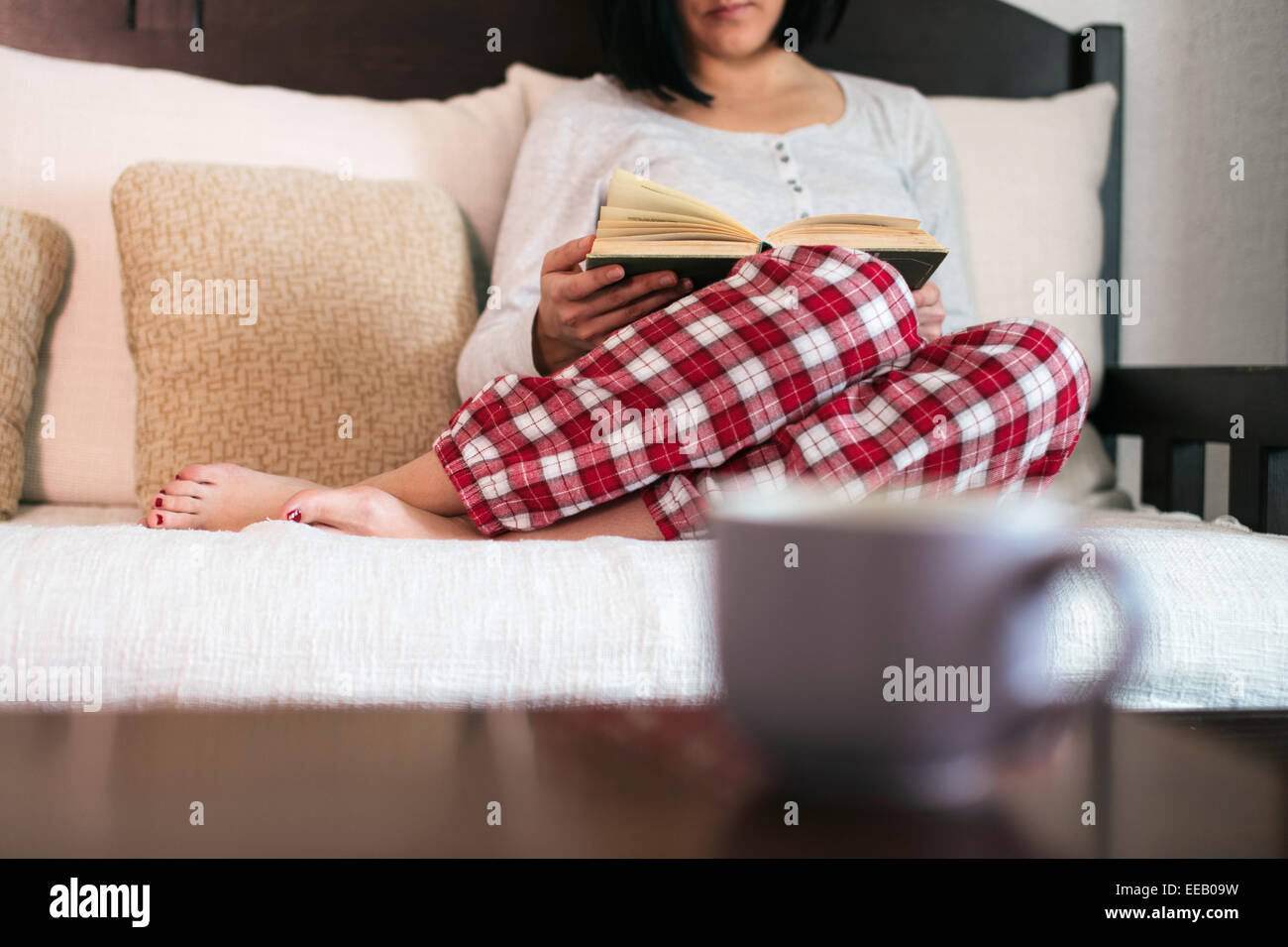 Women in her living room reading book and drinking tea - Stock Image