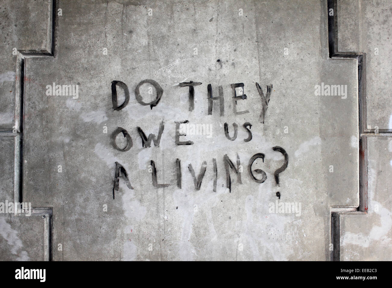 Urban Graffiti 'Do They Owe Us A Living ?' - Stock Image