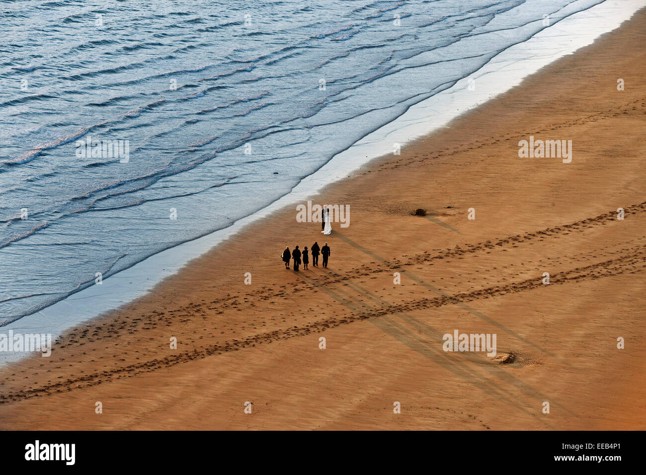 Marriage on beach long shadows sea and sand bride and groom extreme wide shot from above - Stock Image