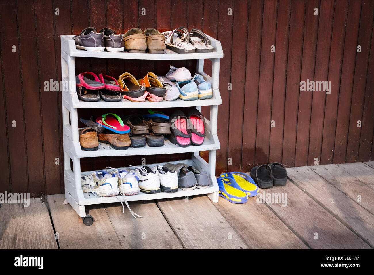 A variety of colorful shoes, neatly ordered on a plastic shoe rack outside a wooden house. - Stock Image