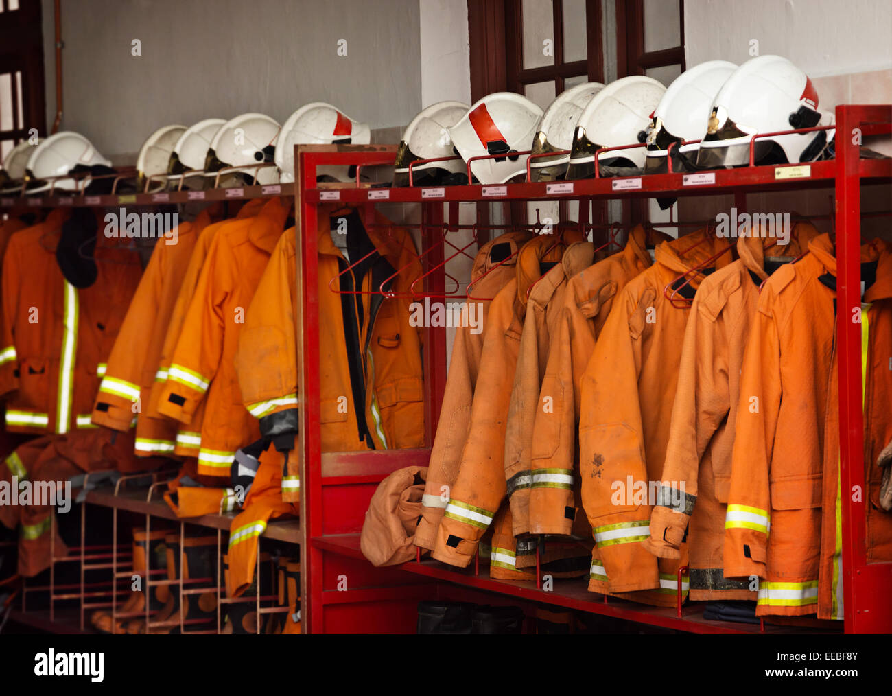 Firefighting safety equipment, including helmets, flame-resistant jackets and boots, arranged on a rack at the Georgetown - Stock Image