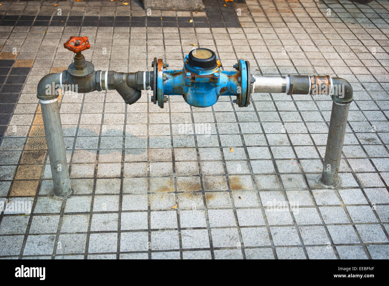Water pipes with a meter and main shutoff valve, protruding from the sidewalk along a public street. - Stock Image