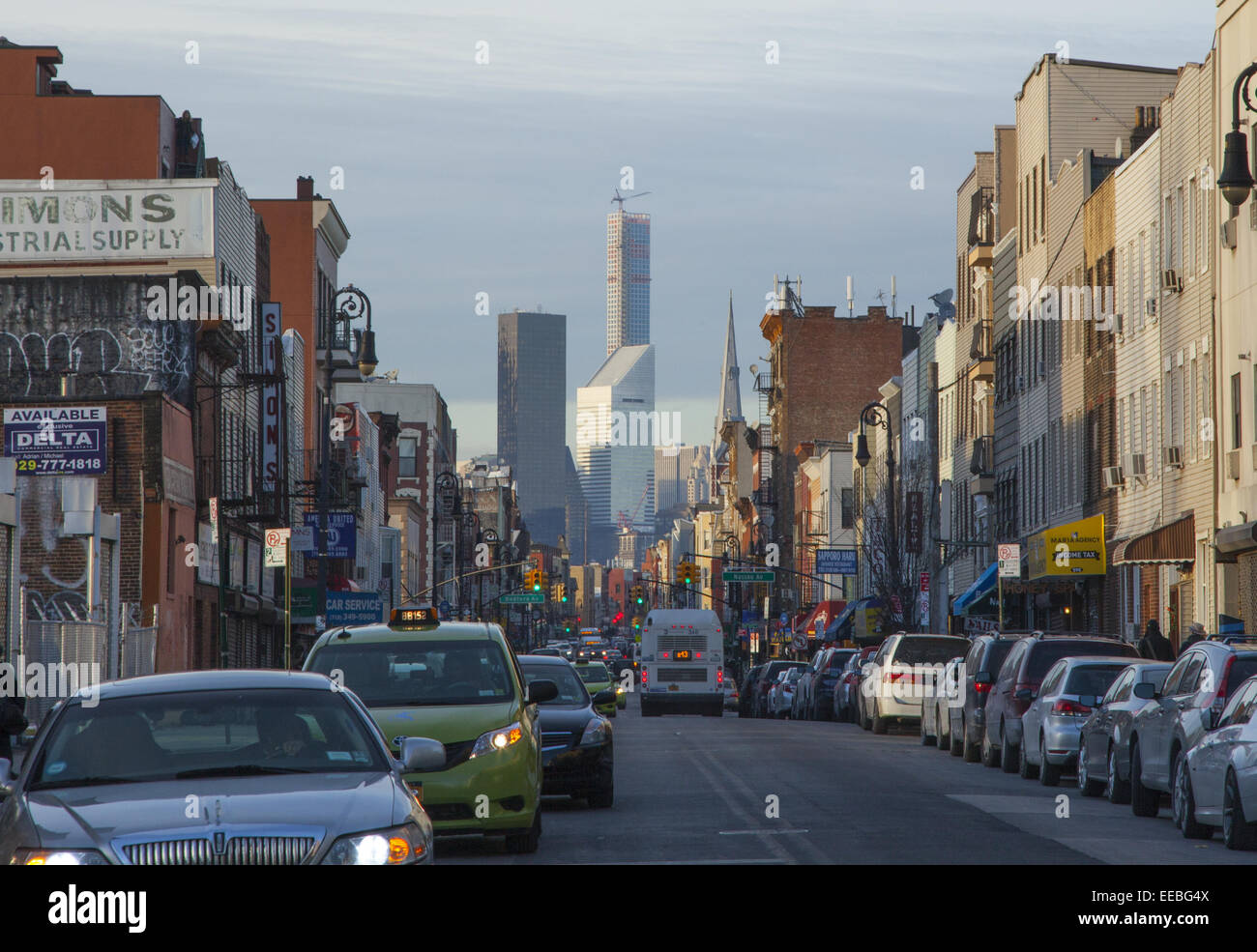Looking up Manhattan Ave in Greenpoint Brooklyn with midtown Manhattan office towers  looming up on the horizon. - Stock Image