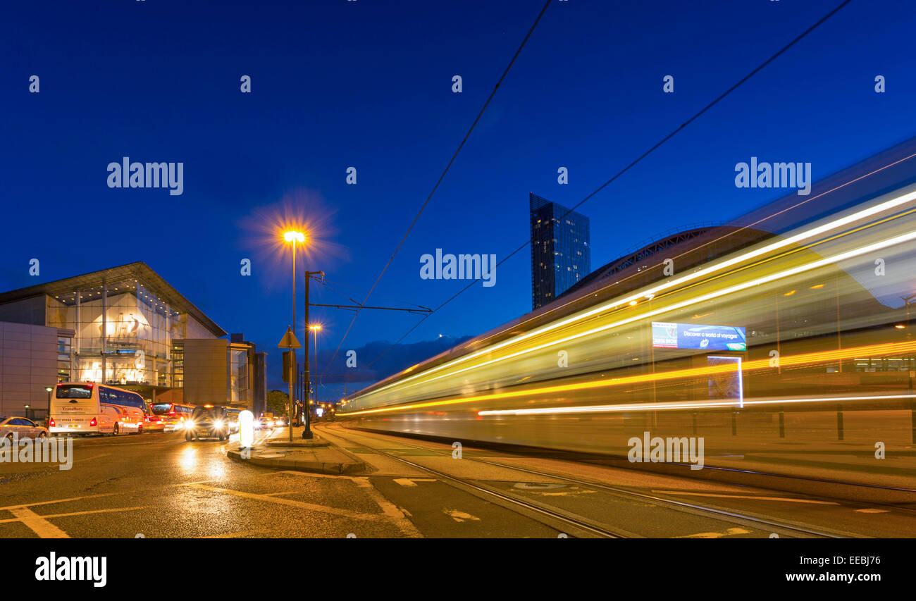 England, Manchester, twilight shot of moving tram and Manchester convention Centre - Stock Image