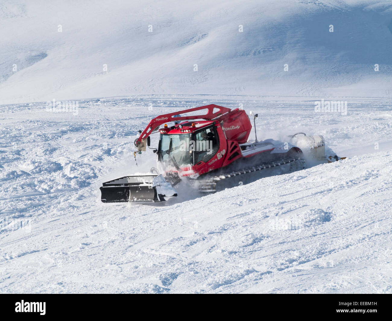 Snow basher or piste grooming bully caterpillar tracked vehicle moving quickly on ski slopes. St Anton am Arlberg Stock Photo