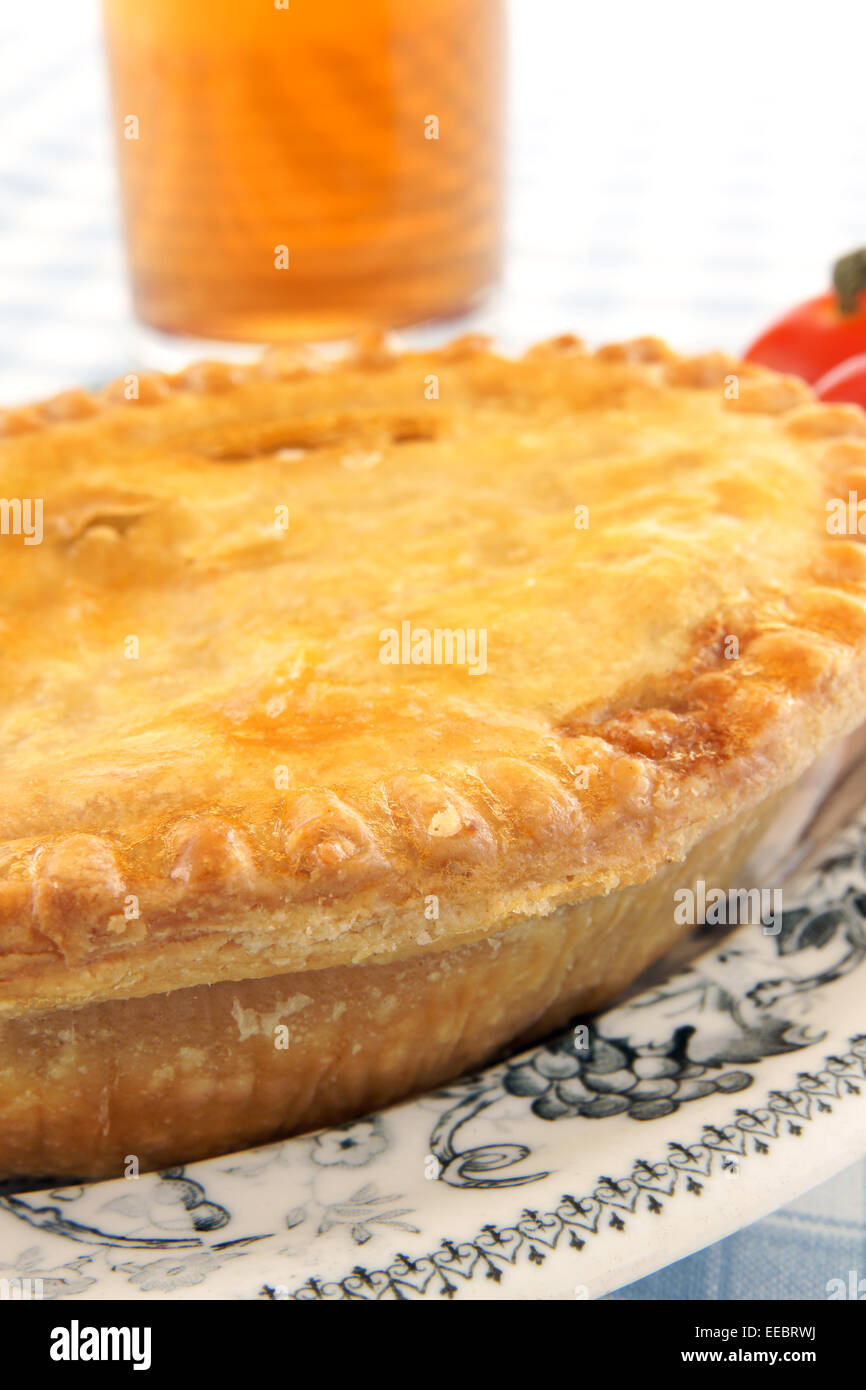 A golden savoury meat pie on an antique plate and glass of beer & A golden savoury meat pie on an antique plate and glass of beer ...