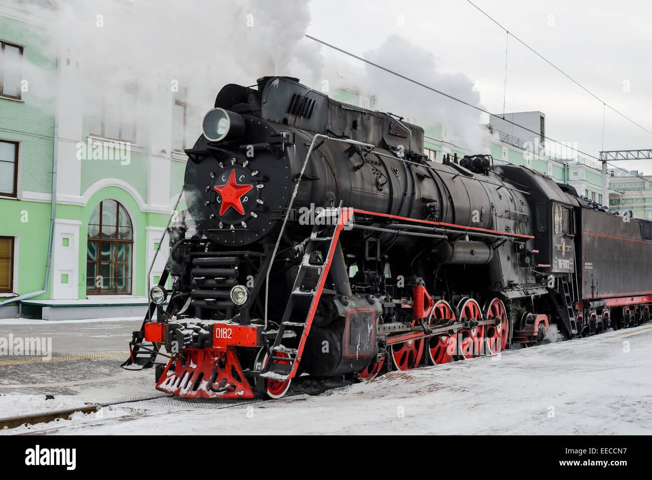 Old steam locomotive at railroad platforn in winter Stock Photo