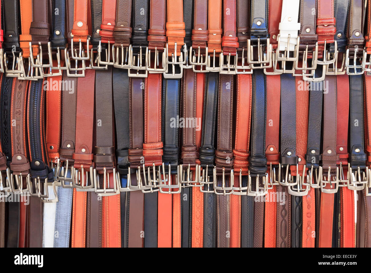 A collection of unbranded belts on a market stand - Stock Image