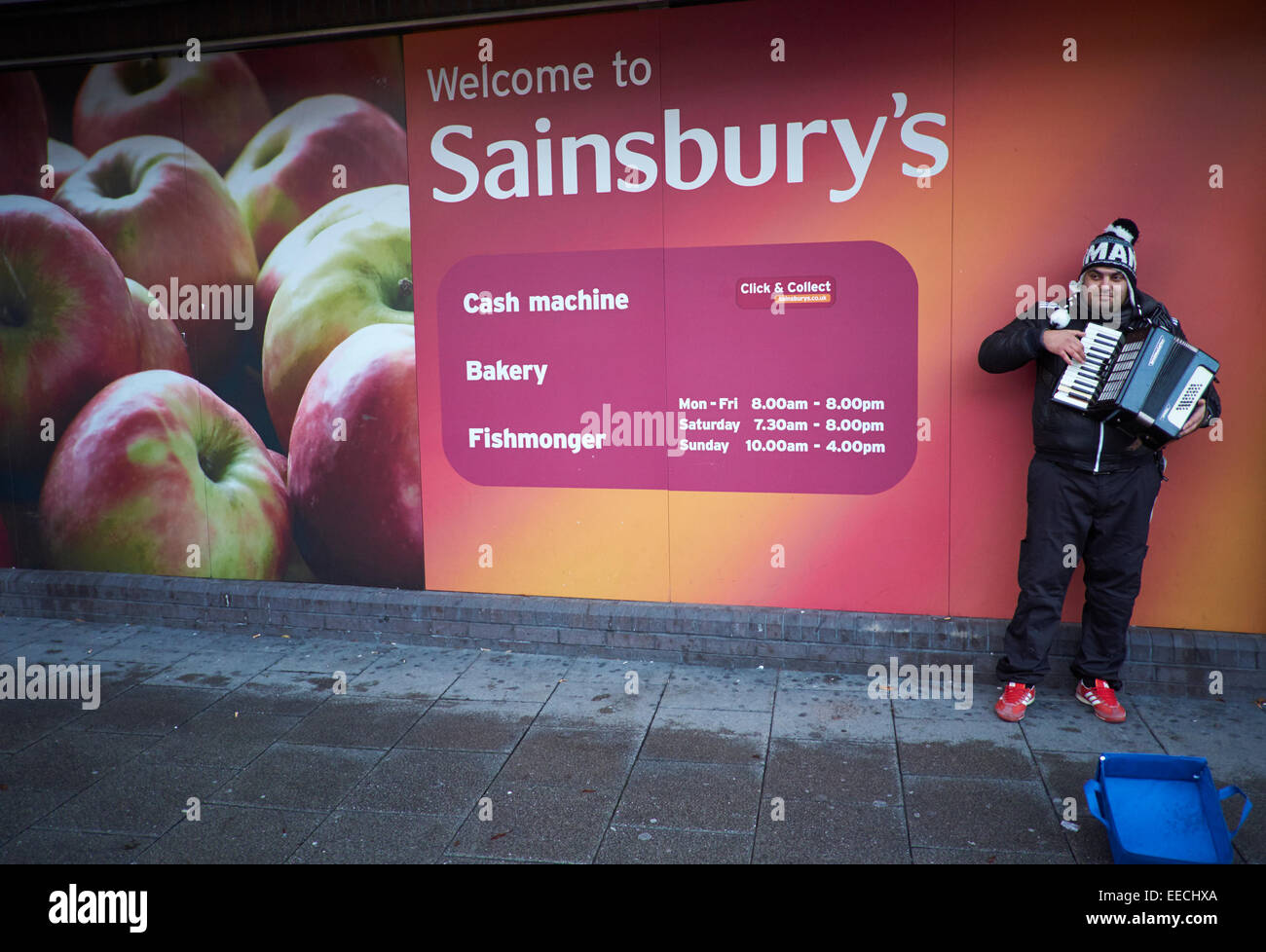 Stockport town centre Sainsbury's store, a busker performs with his Accordion - Stock Image