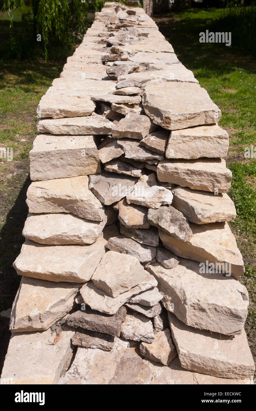 Newly built dry stone wall constructed of new Cotswolds stone using traditional old methods, UK - Stock Image