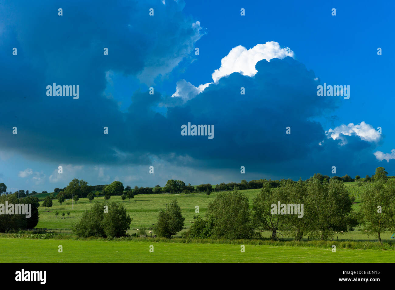 Skyscape - storm cloud darkens blue sky and loom over the landscape in summer, The Cotswolds, UK - Stock Image