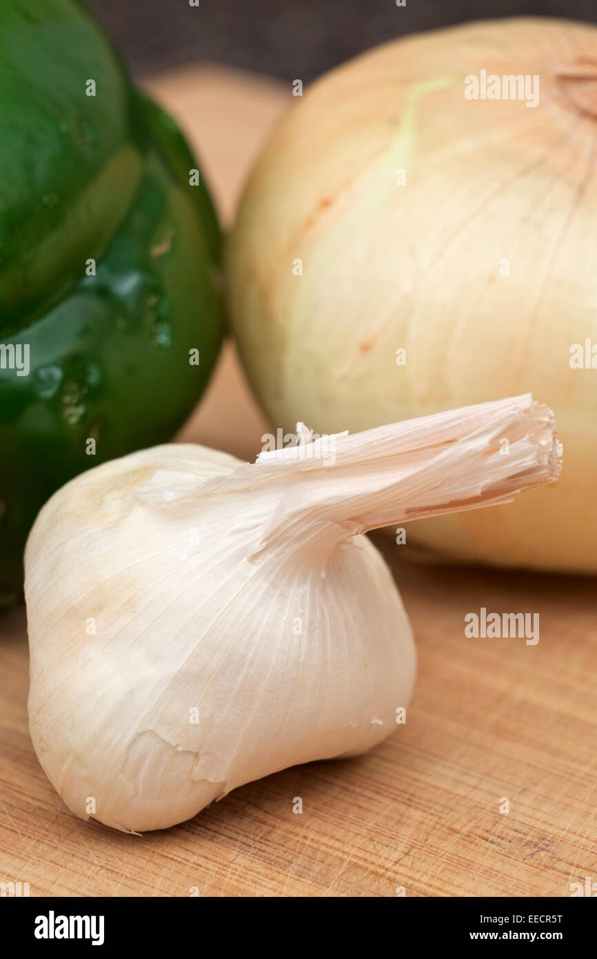 Whole garlic clove with a sweet onion and green bell pepper in backgraound - Stock Image