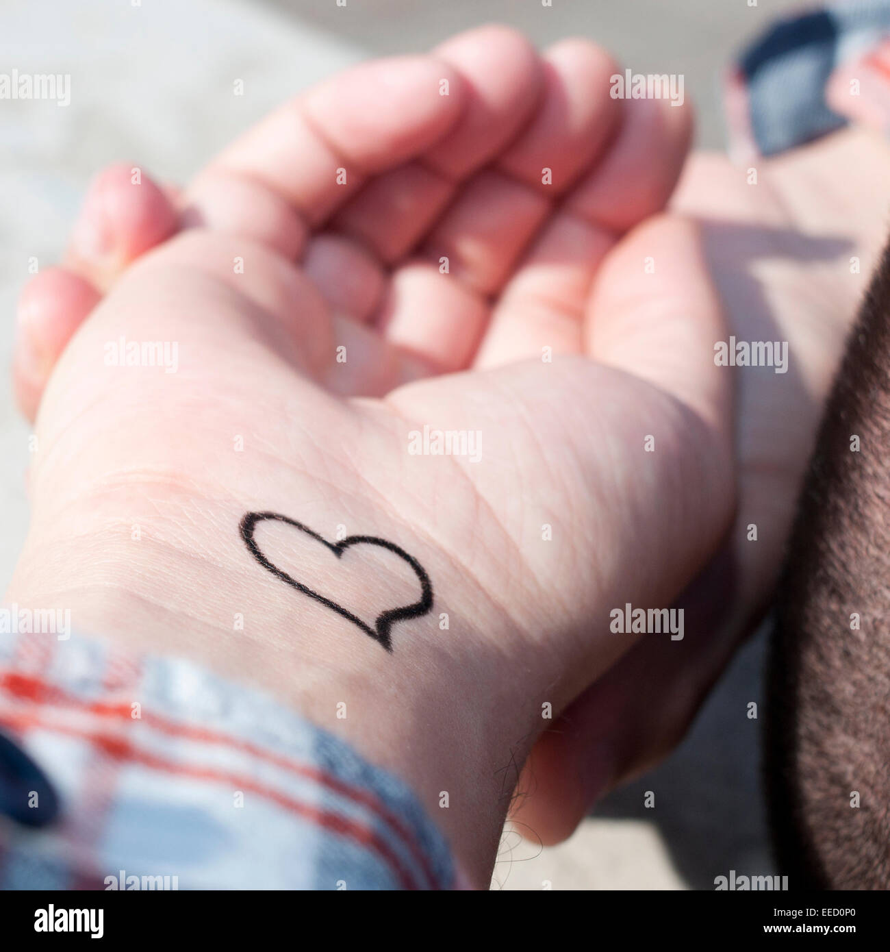 closeup of the wrist of a young man with a heart tattooed in it - Stock Image
