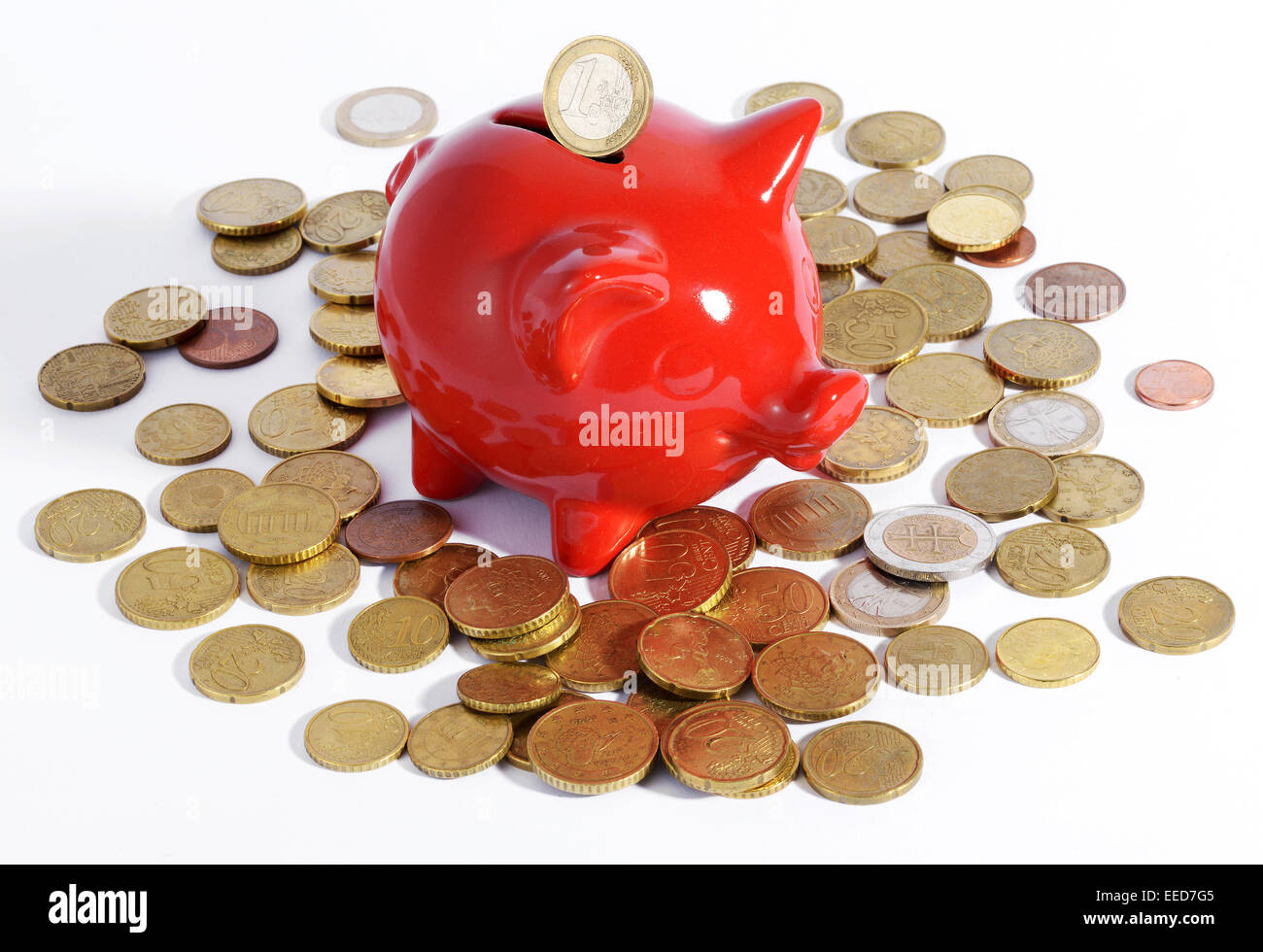 Red piggy bank surrounded by coins - Stock Image