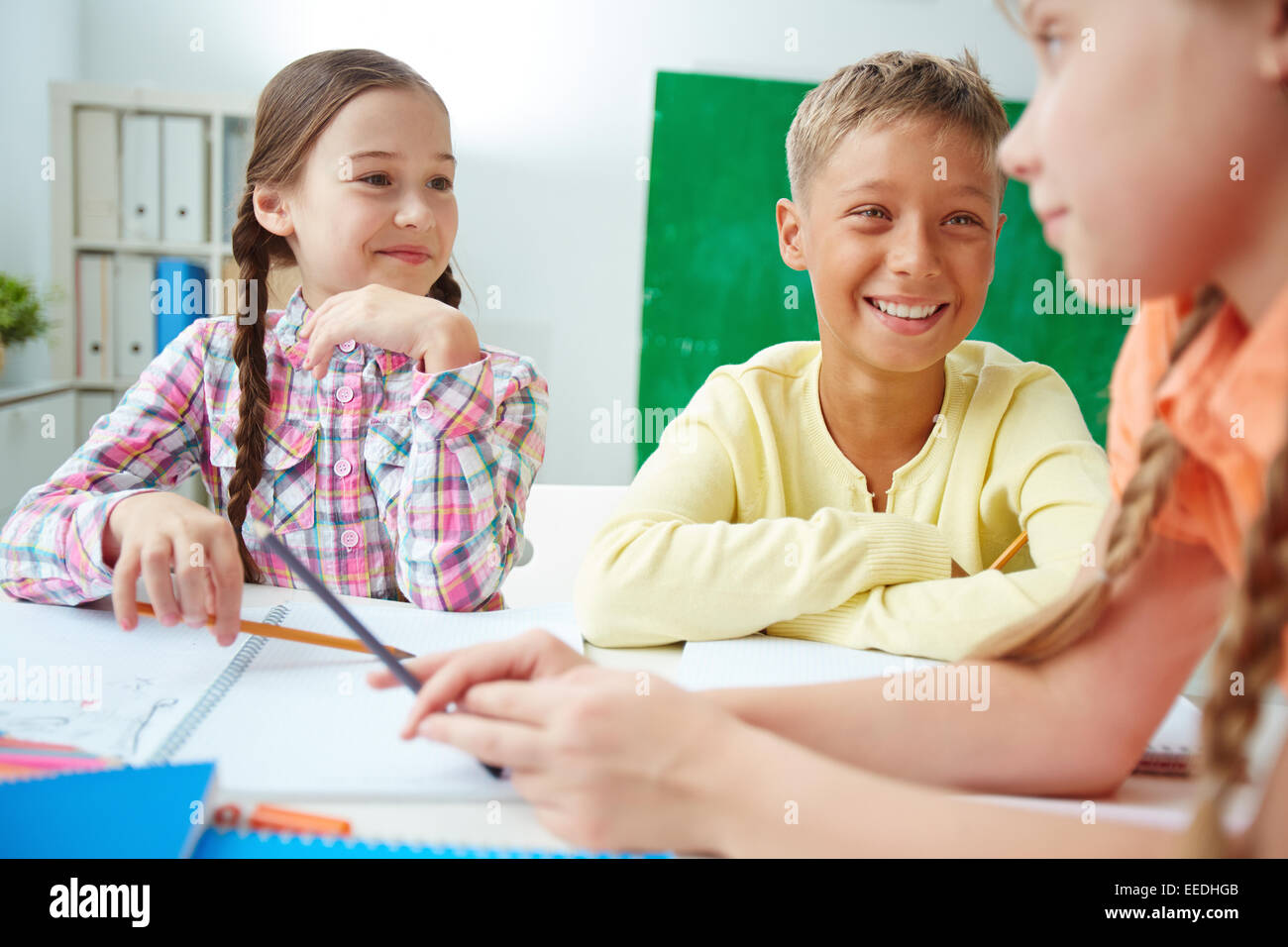 Group of adorable schoolmates discussing ideas at drawing lesson - Stock Image