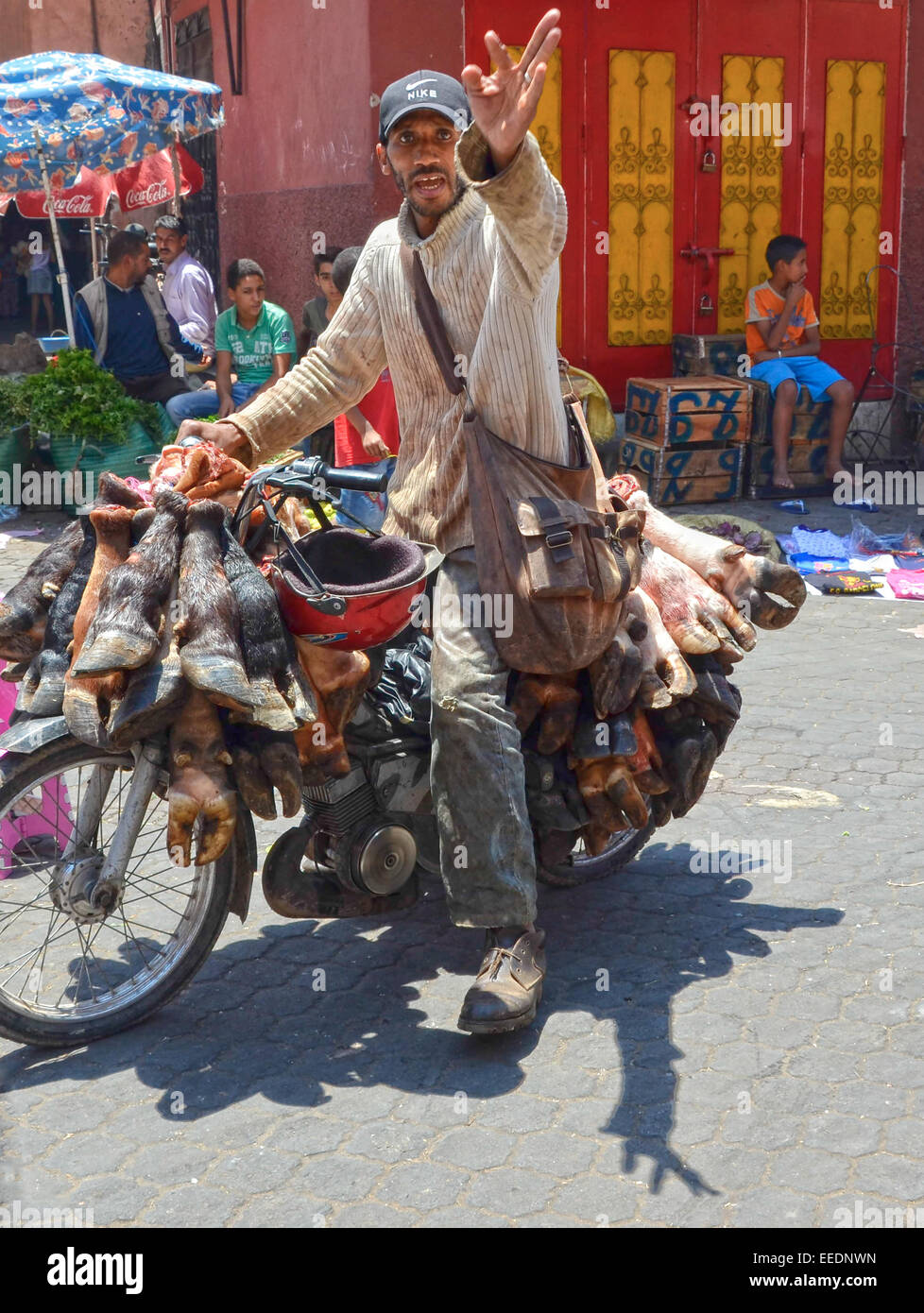 Angry motorbike rider carrying the hooves and shins on cattle across the Marrakesh market berates tourists in his - Stock Image