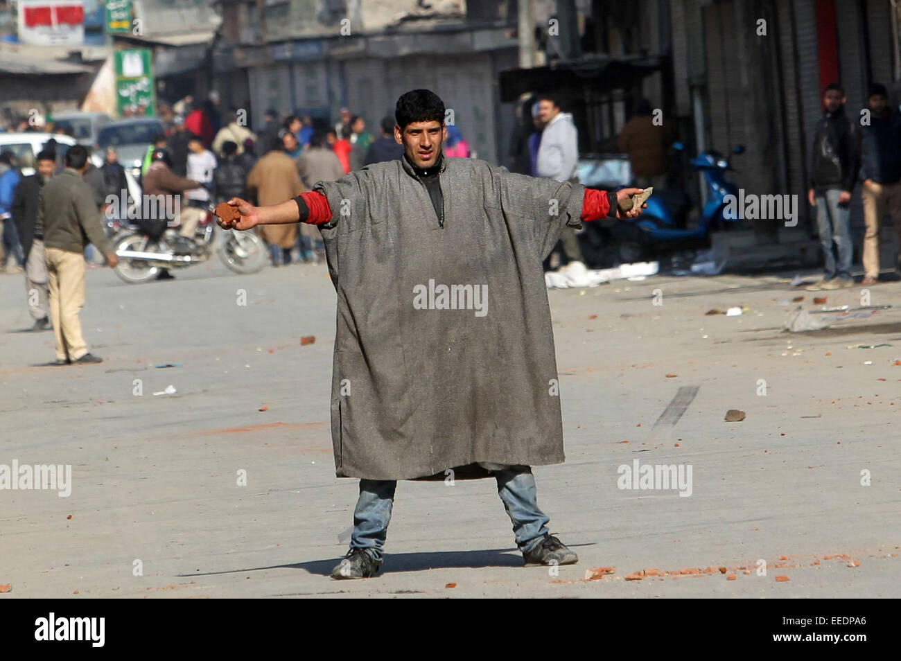 Srinagar, Kashmir. 16th January, 2015. A Kashmiri protestor holds stones in his hands as he gestures towards Indian - Stock Image