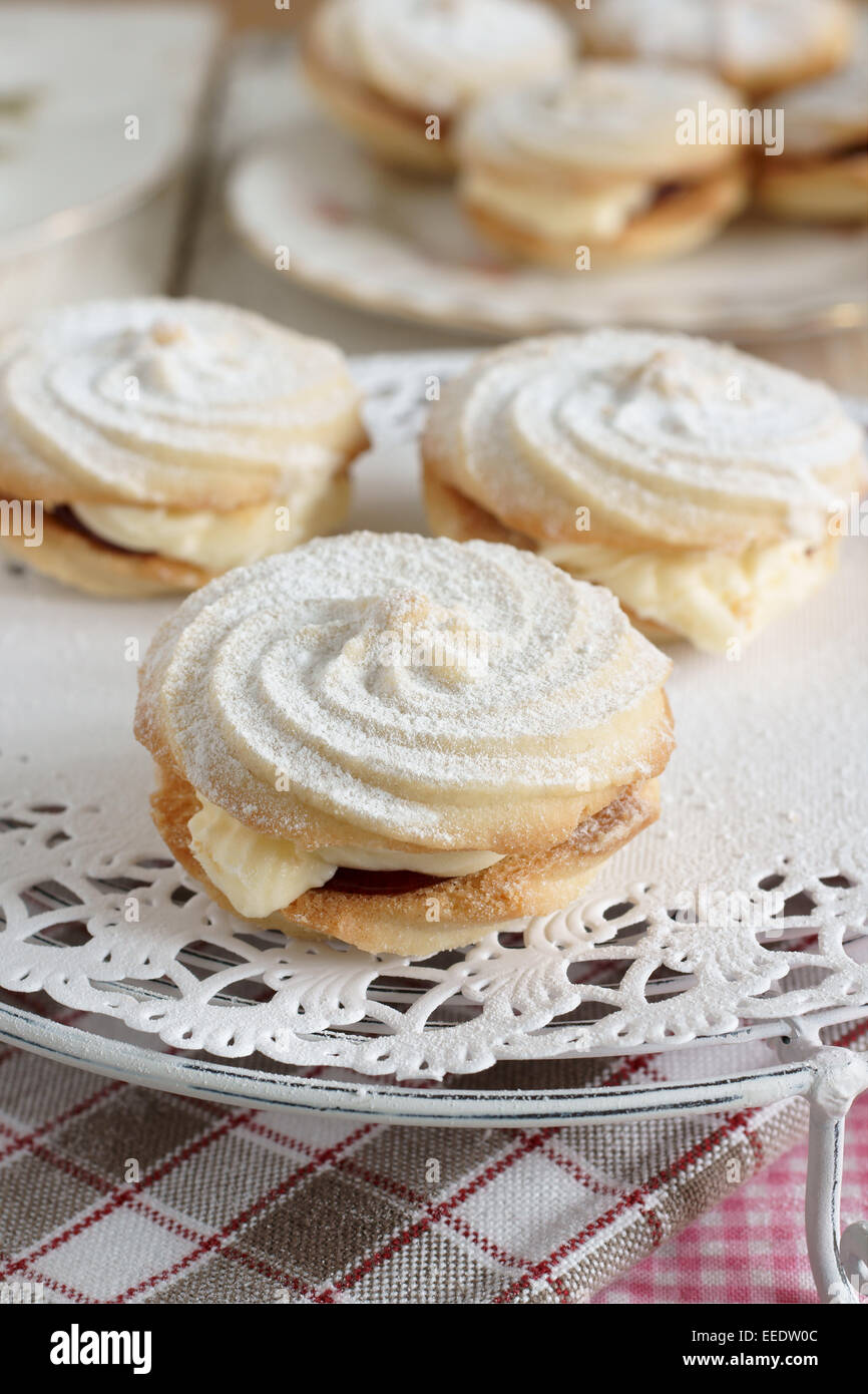 Viennese Whirls a British confection made of a soft butter biscuit piped into a whirl shape filled with buttercream - Stock Image