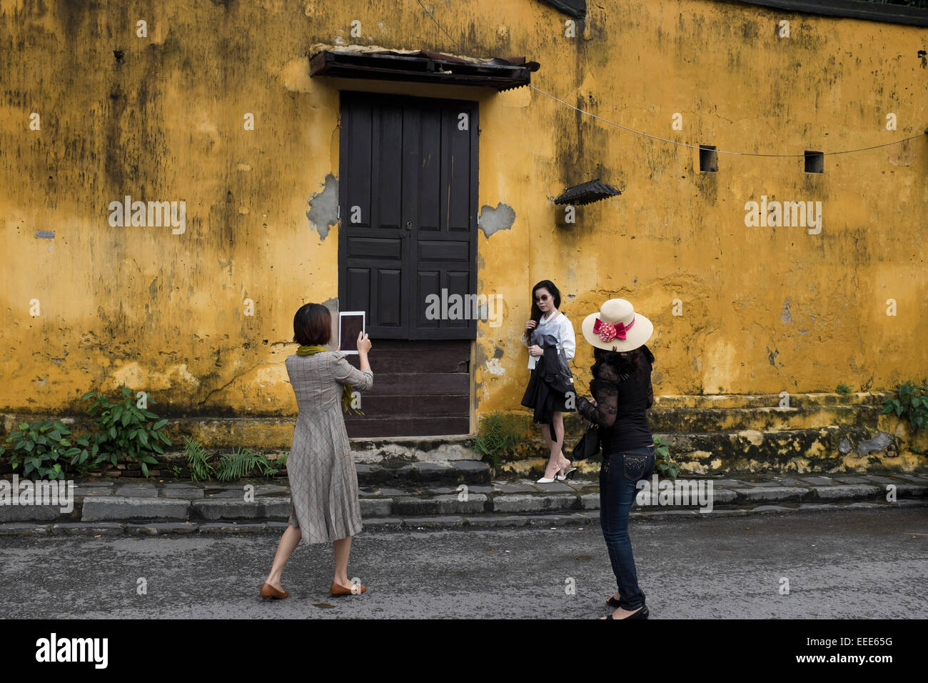 Tourists taking photos of each other in Hoi An Stock Photo