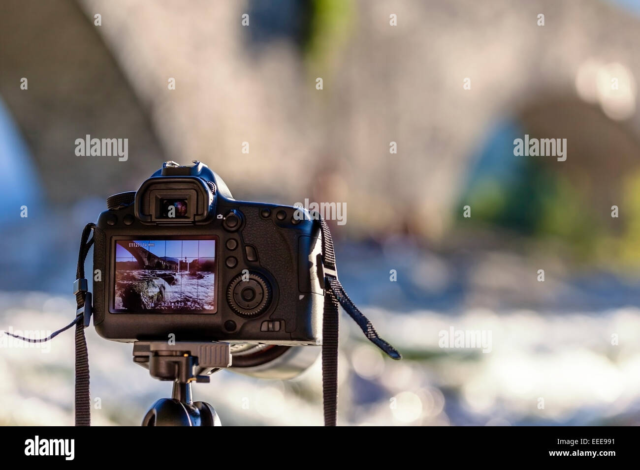 A DSLR camera on a tripod shooting a bridge landscape. Ponte ...