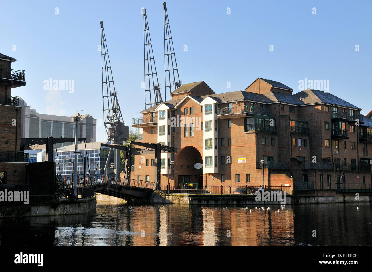 Apartment buildings on Pepper St and lift bridge between Millwall Inner and outer Docks in London Canary Wharf - Stock Image