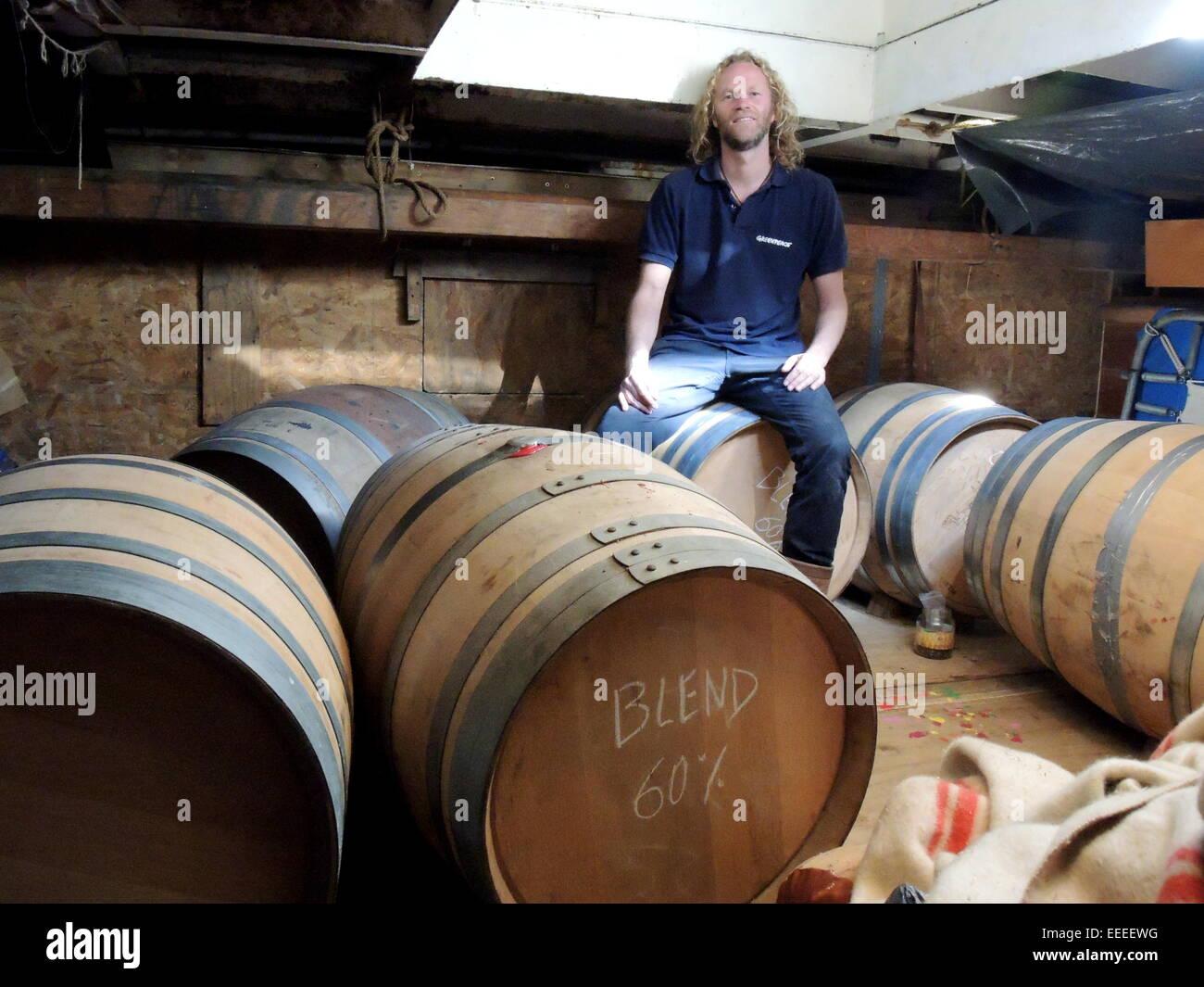 Arjen van der Veen, dutch copartner of the fairtrade society 'Tres hombres', sitting on barrels of rhum - Stock Image